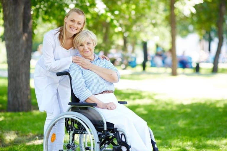 Mantelzorger loopt rondje met moeder in rolstoel